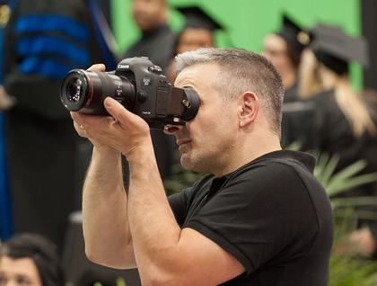 Buffalo State photographer taking photographs at commencement