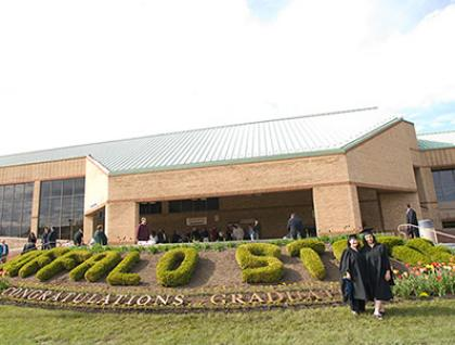 Buffalo State sports complex with commencement garden in foreground