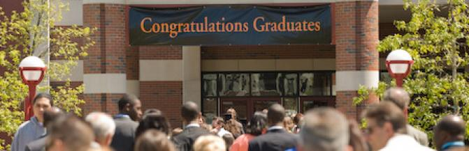 Congratulations Graduates banner outside the Campbell Student Union with crowd of commencement guests and graduates