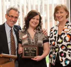 student receiving arts and humanities award with faculty presenters