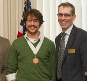 student receiving excellence award from dean and faculty