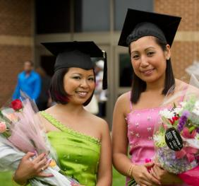 two graduates with caps posing and holding flower bouquets