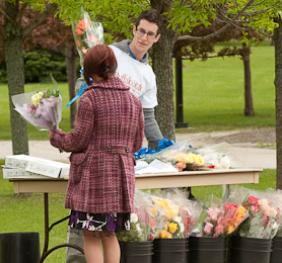 a commencement guest purchasing a flower bouquet at the sales table outside the sports arena