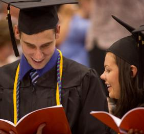 two graduates reading commencement program at the ceremony
